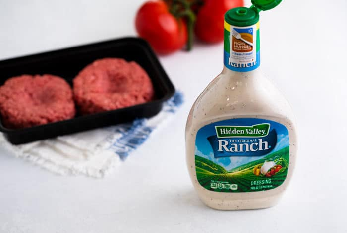 A bottle of Hidden Valley Ranch Salad Dressing with two uncooked burger patties and tomatoes in the background.