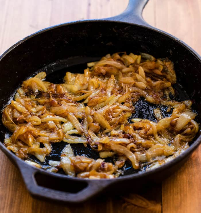 Caramelized onions in a black cast iron pan on a wooden surface.