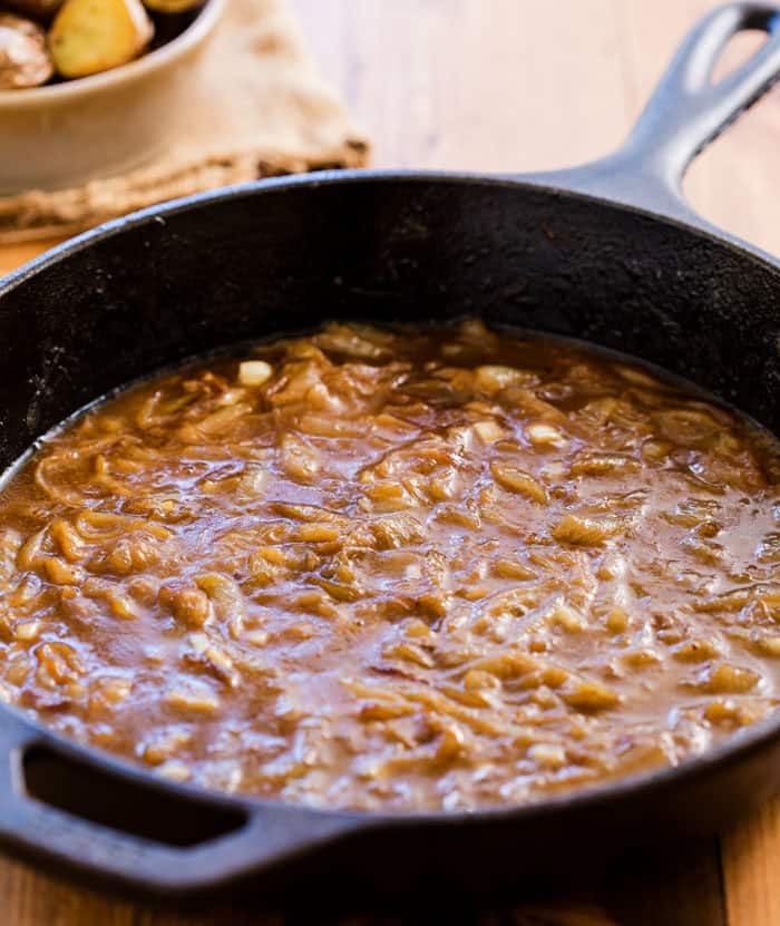 French Onion Sauce in a black cast iron skillet on a wooden surface.