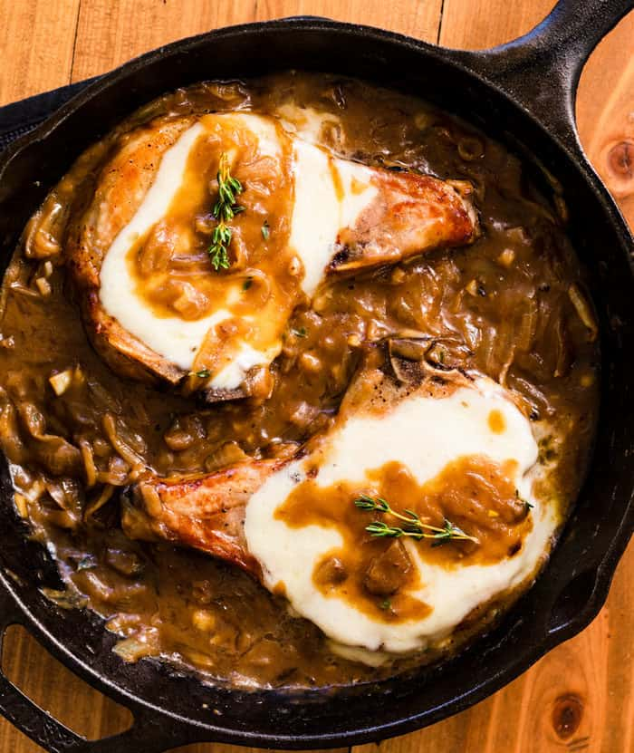 Overhead view of 2 pork chops in a black cast iron skillet topped with melted cheese and rosemary in a french onion sauce.