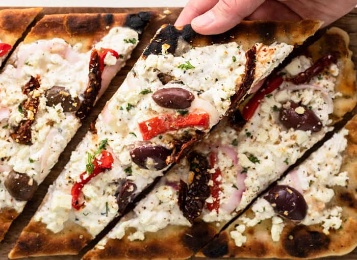 Grilled Flatbread Pizza with a hand pulling up a slice.