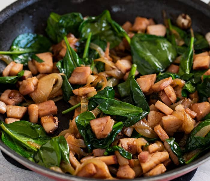diced ham in a pan with caramelized onions and spinach.
