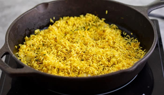Rice crisping up in a black cast iron skillet, yellow from turmeric