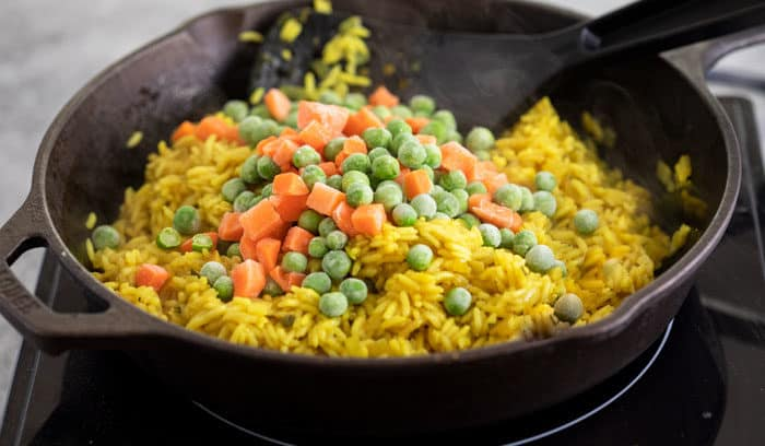 Frozen peas and carrots being added to yellow colored cooked rice in a black cast iron skillet.