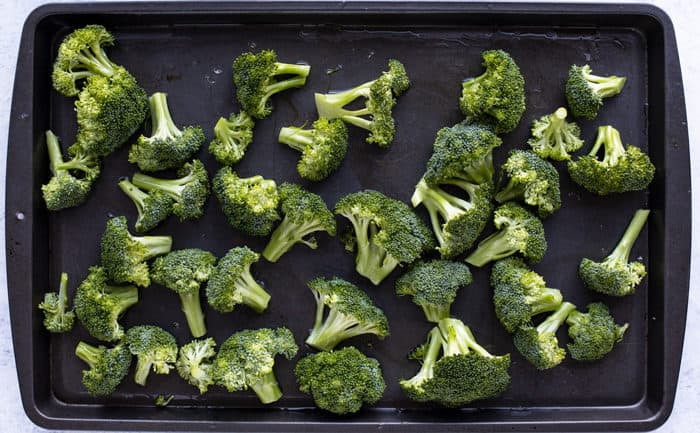 A cookie sheet full of fresh broccoli.