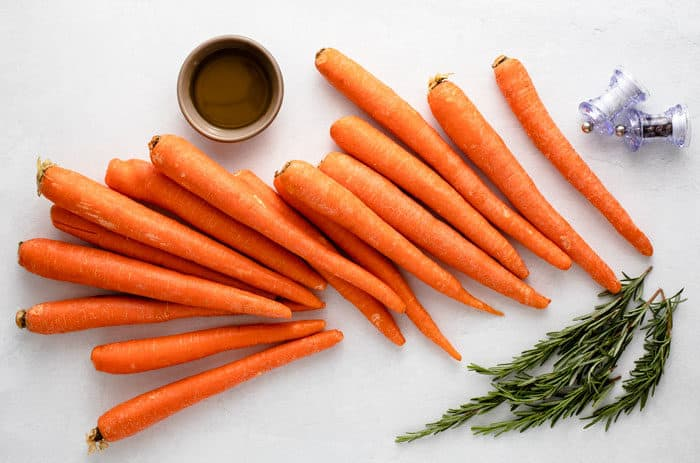 whole, unpeeled carrots on a white surface with fresh rosemary and salt and pepper.