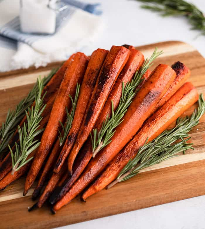 Roasted carrots on a wooden cutting board with fresh rosemary.