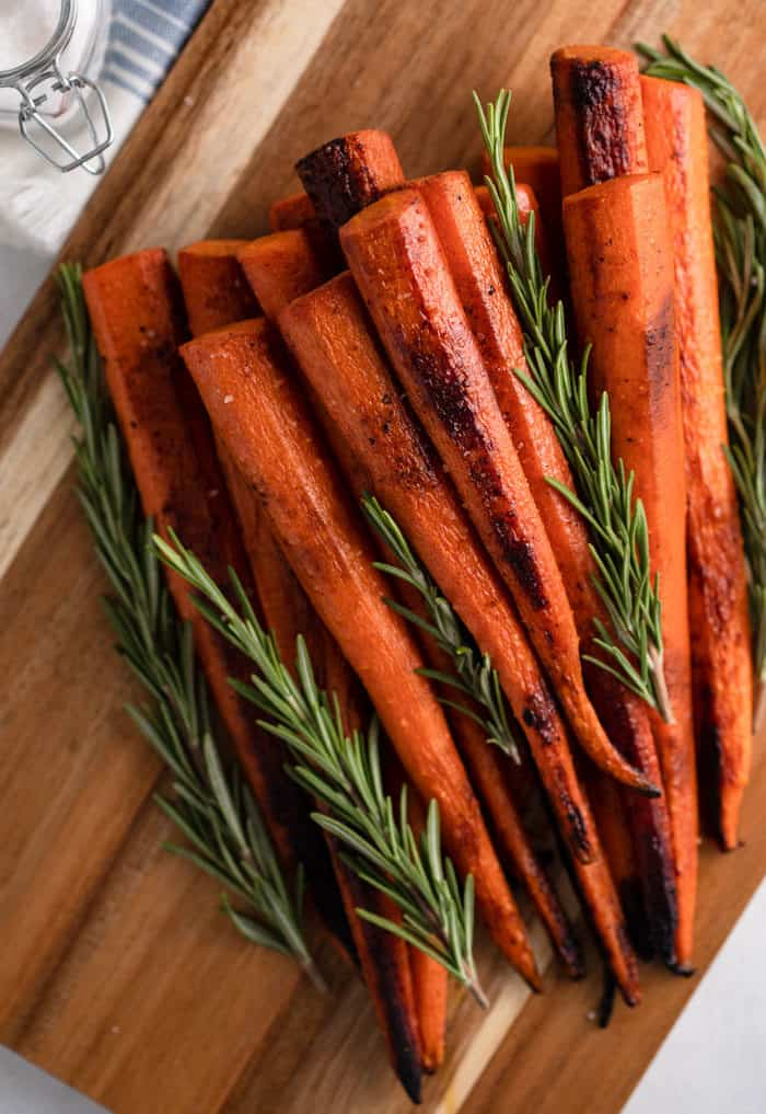 Overhead view of roasted carrots and fresh rosemary on a wooden cutting board.