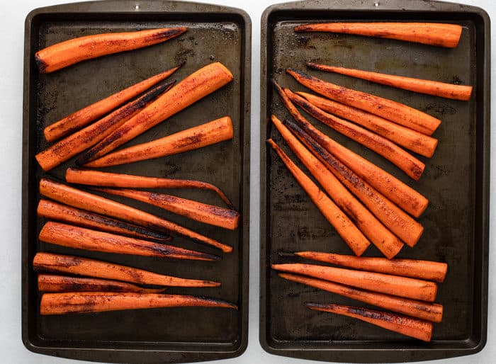 Whole, roasted carrots on two dark baking sheets after roasting in the oven.