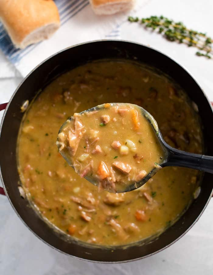 Overhead view of ladle full of split pea soup in a large soup pot.