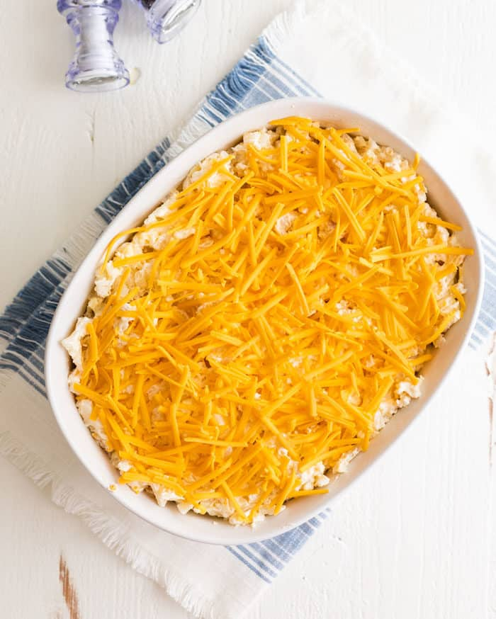 Overhead view of unbaked hashbrown casserole topped with cheese on a white and blue dish cloth on a white wooden table.