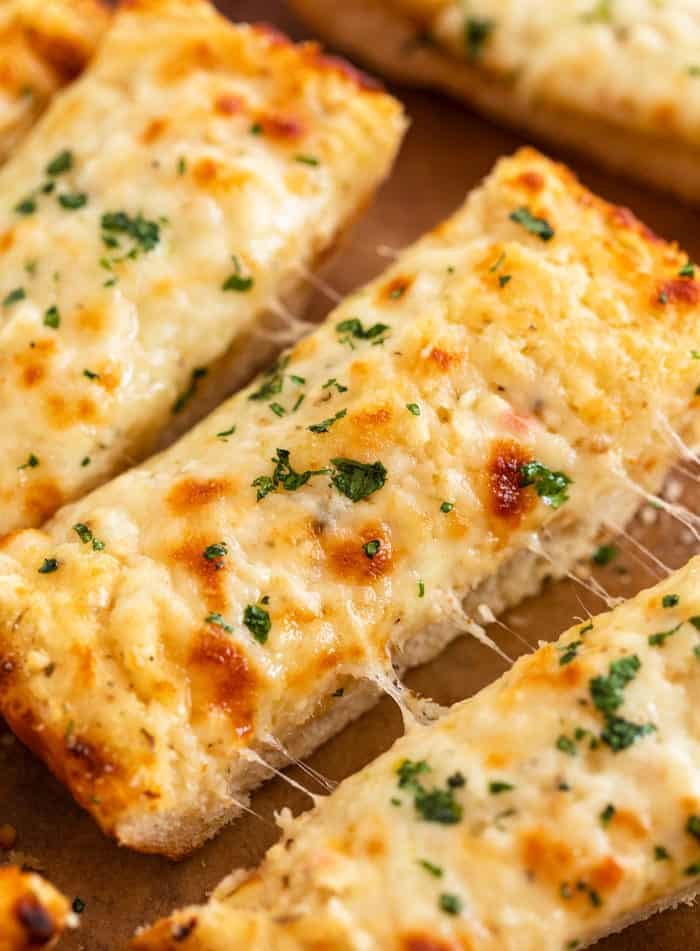 Slices of Cheesy Garlic Bread topped with parsley.