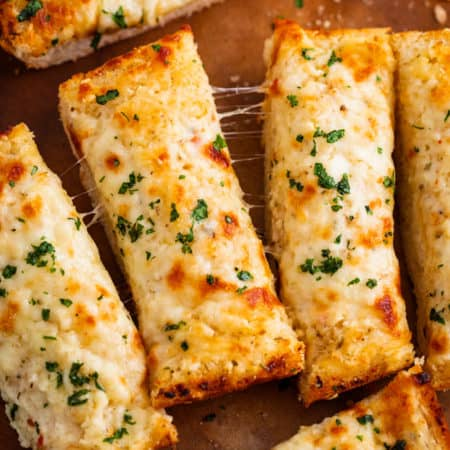 Slices of Cheesy Garlic Bread topped with cheese on a wooden cutting board.