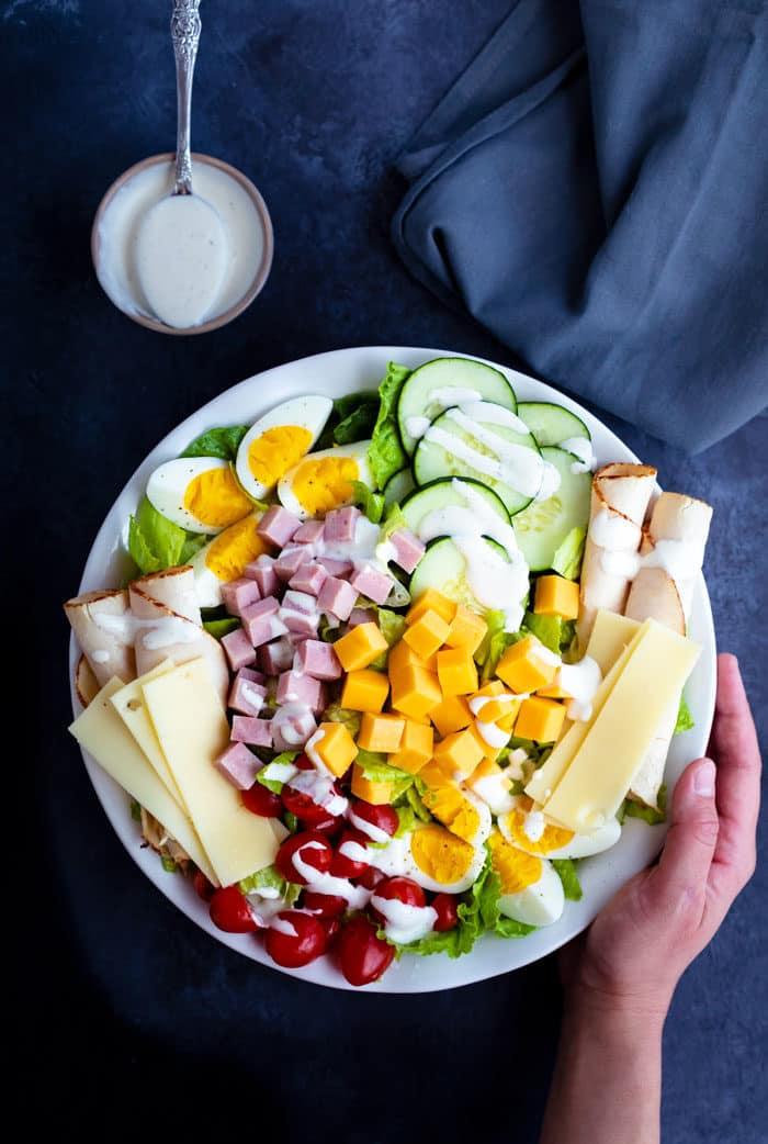 Overhead view of a white plate full of colorful chef's salad with a hand holding the side of the plate. The background is dark blue, there is a cup of ranch dressing to the side of the plate.