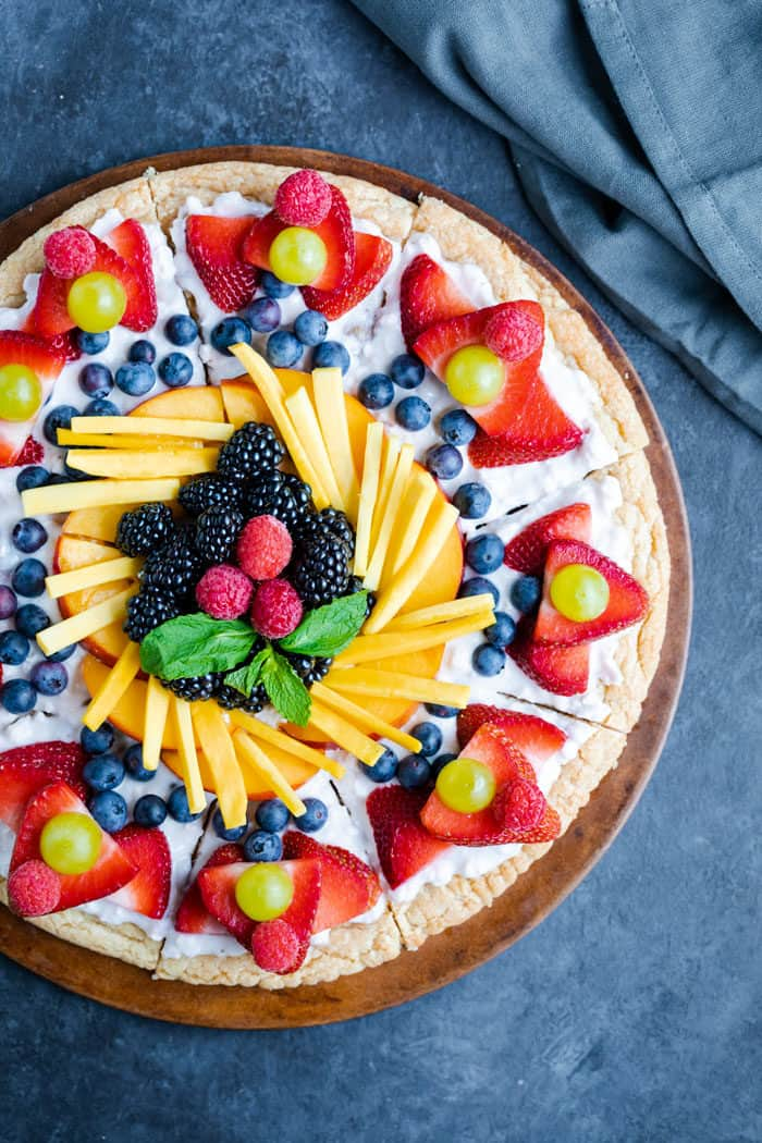 overhead image of a bright and colorful fruit pizza on a bright blue background.