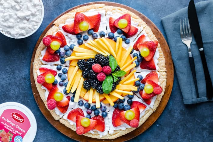 Overhead view of a round fruit pizza on a blue surface next to a knife and a fork and a tub of cottage cheese.