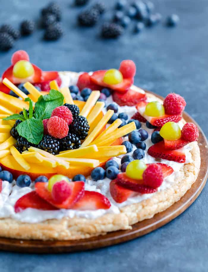 Close up view of the top of a bright and colorful fruit pizza on a blue surface with fruit in the background.