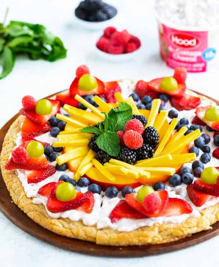 A bright and colorful fruit pizza on a white surface with cups of fruit and cottage cheese in the background.