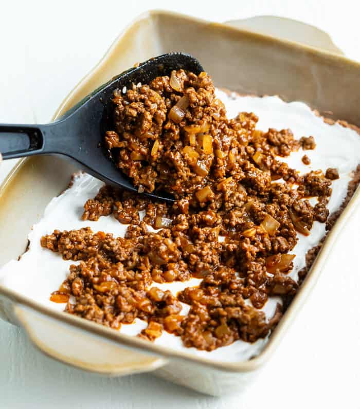 A big spatula spooning seasoned ground beef into a casserole dish for taco casserole.
