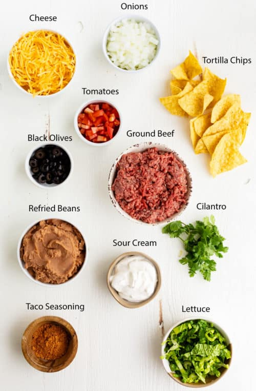 Overhead view of ingredients needed to make taco casserole on a white surface.