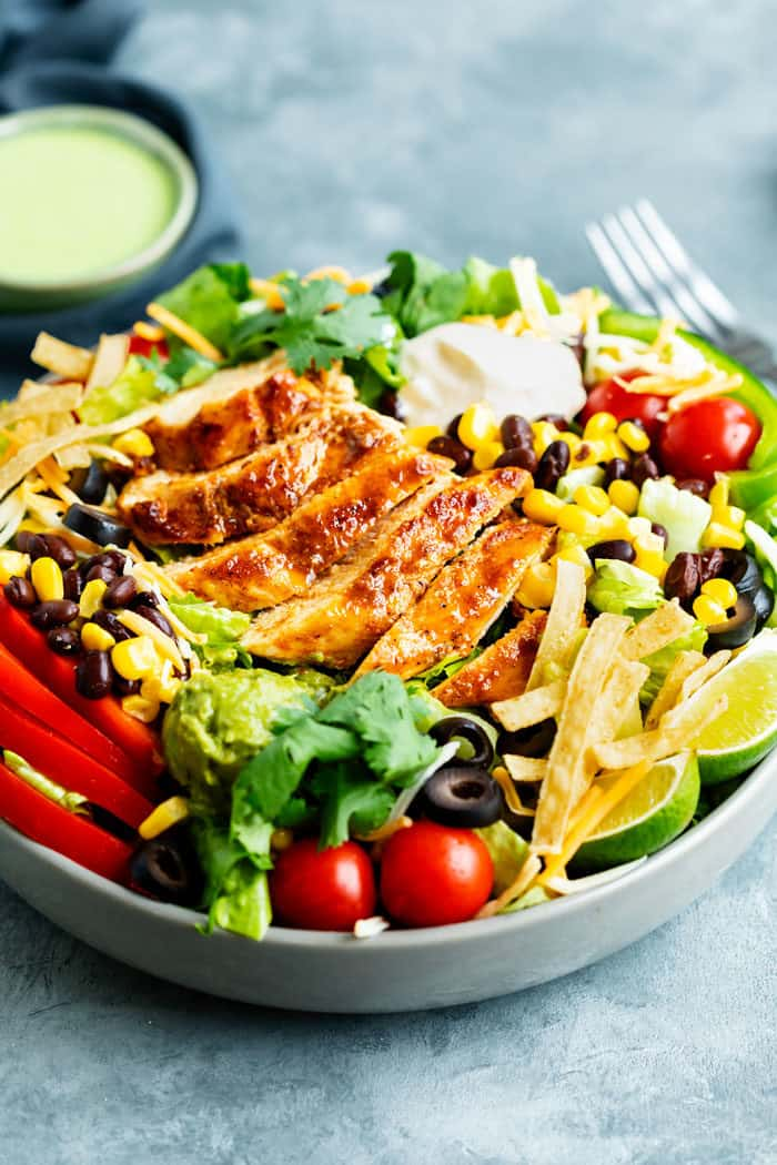 Close up view of a big bowl of Southwest salad with seared chicken on top.