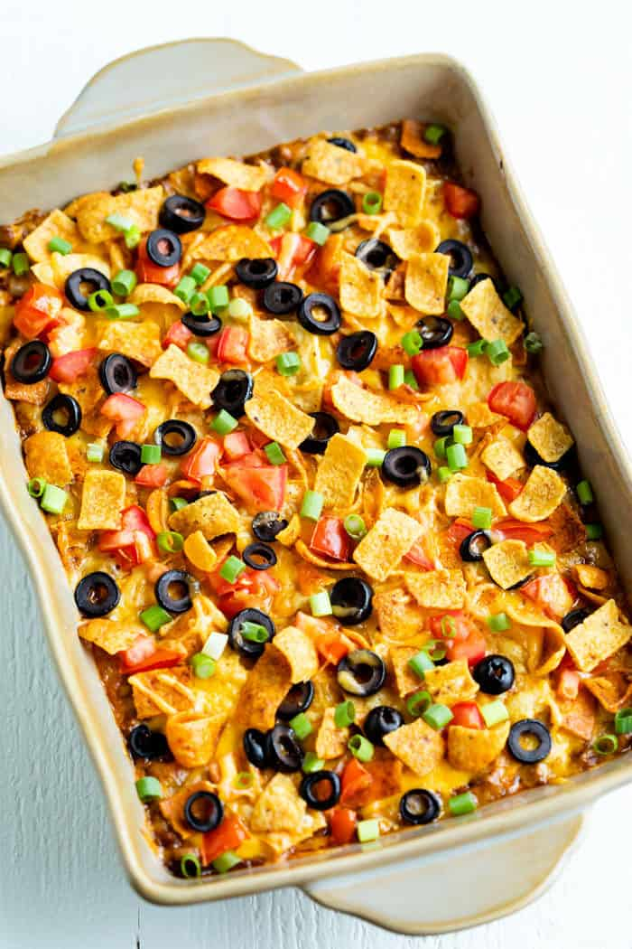Overhead view of Taco Casserole in a casserole dish topped with fritos, tomatoes, and black olives.