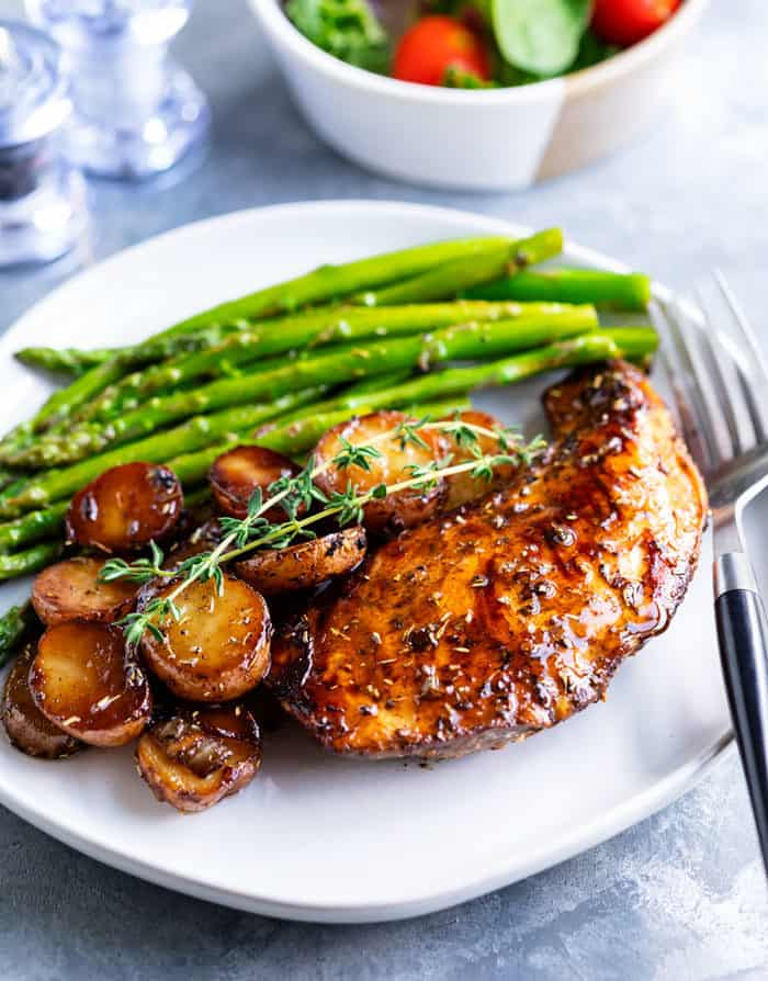 Balsamic chicken on a white plate with potatoes and asparagus.