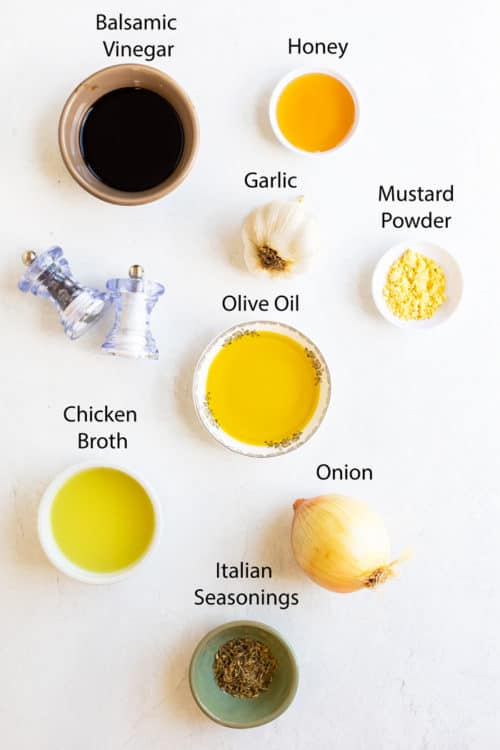 Overhead view of ingredients needed to make balsamic marinade on a white surface.