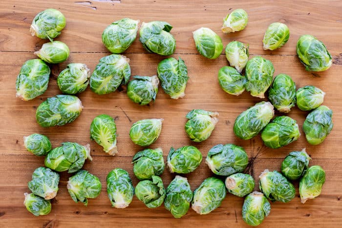 whole, uncooked Brussels sprouts on a wooden table.