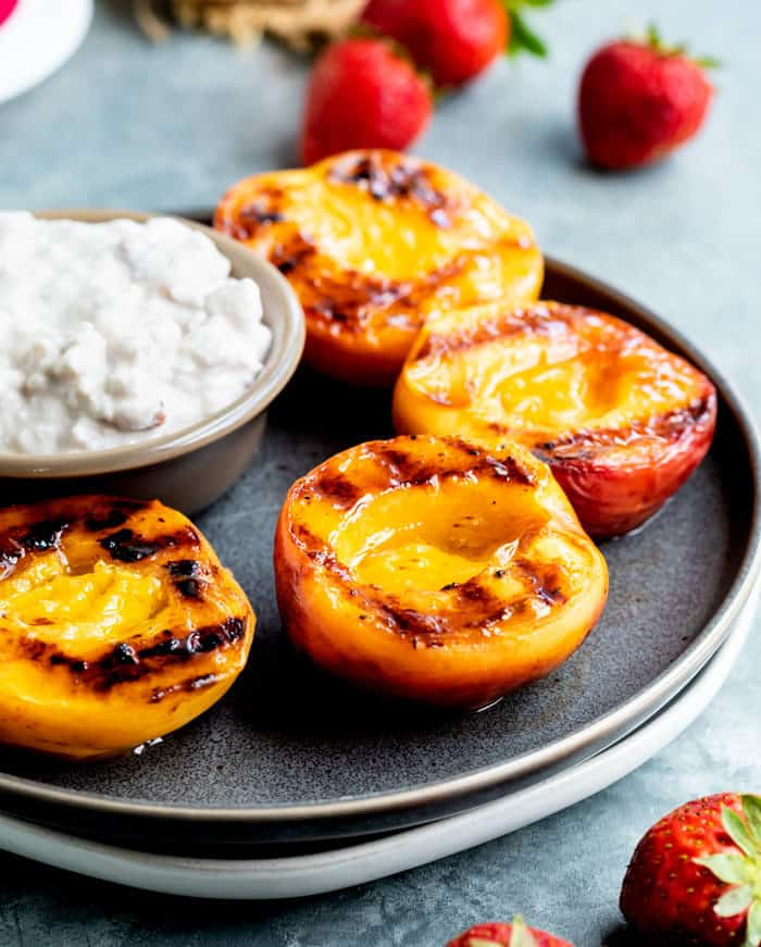 Juicy, grilled peaches on a plate next to a ramekin of cottage cheese with strawberries in the background.