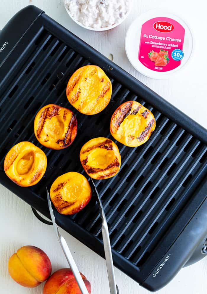 An indoor grill and kitchen tongs grilling peaches on a white surface with a container of cottage cheese.