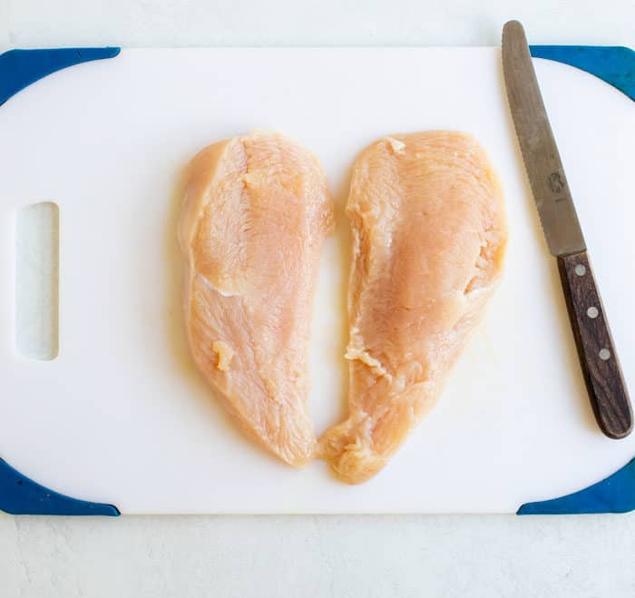A halved Chicken Breast on a white cutting board next to a knife.