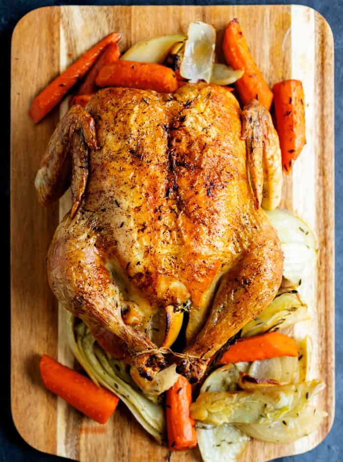 Overhead view of a cooked roasted chicken on a wooden cutting board surrounded by vegetables.