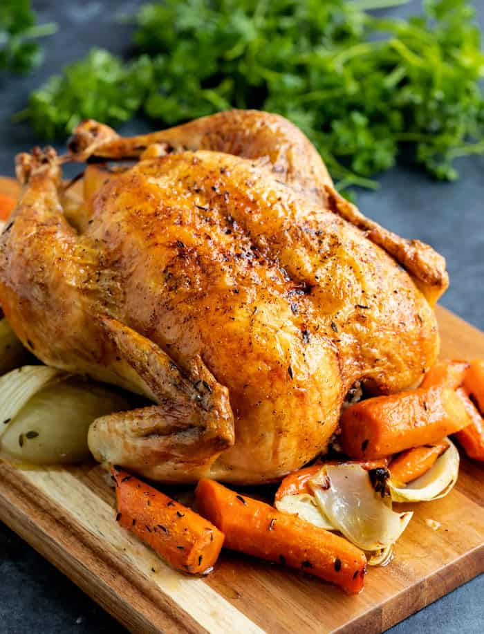 A brown roasted chicken on a wooden cutting board with carrots and onions, and parsley in the background.
