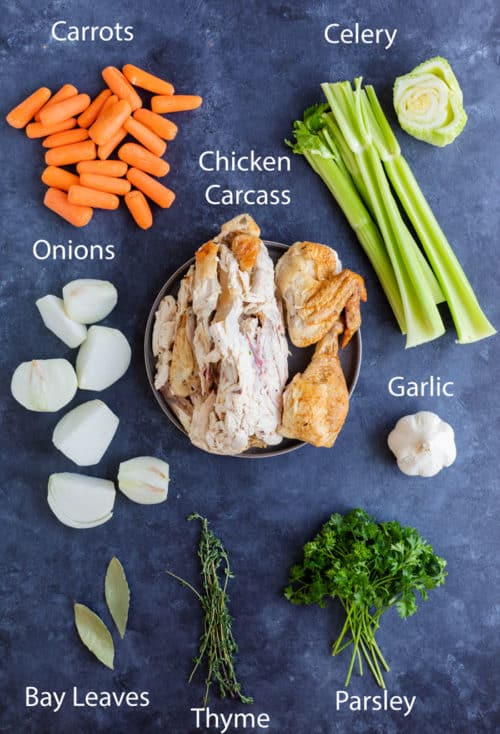 Overhead view of ingredients needed to make homemade chicken stock on a blue surface.