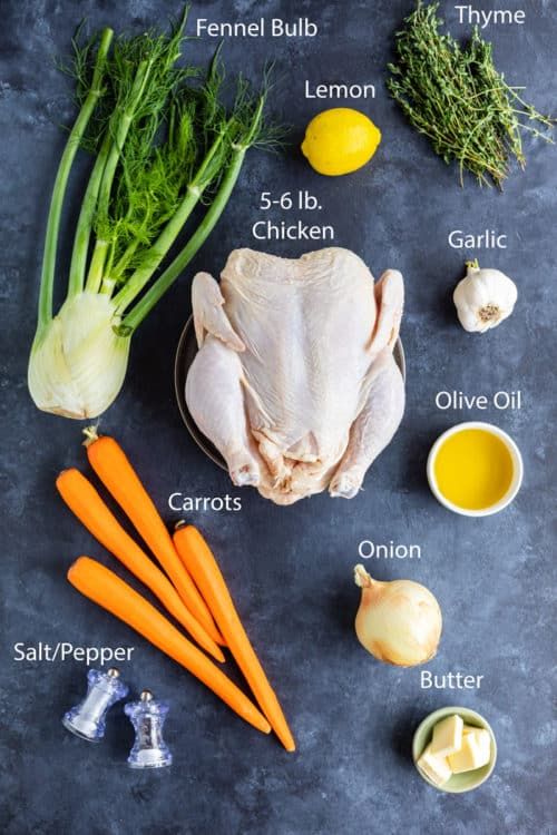 Ingredients needed to make roast chicken lying on a blue surface.