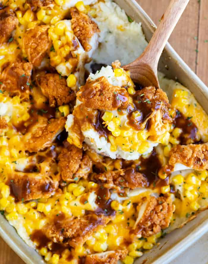 Casserole dish filled with mashed potatoes, corn, crispy chicken, cheese, and gravy with a wooden spoon scooping it out.