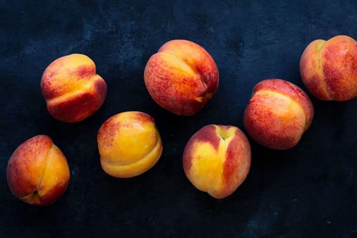 Ripe peaches on a dark blue surface.