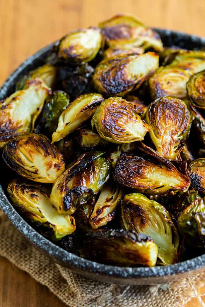 A black bowl filled with roasted brussels sprouts.