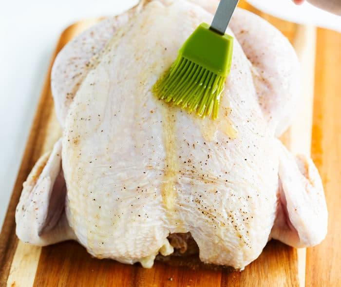 A raw chicken on a wooden cutting board with a green pastry brush spreading melted butter over the top.