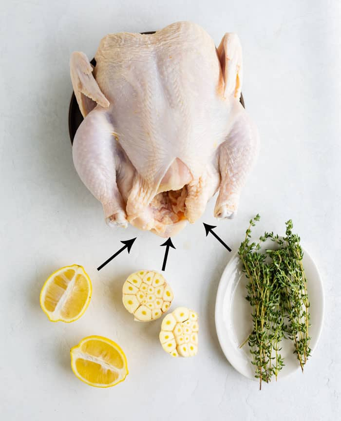 A raw chicken on a white surface with thyme, lemon, and garlic for stuffing the chicken with.
