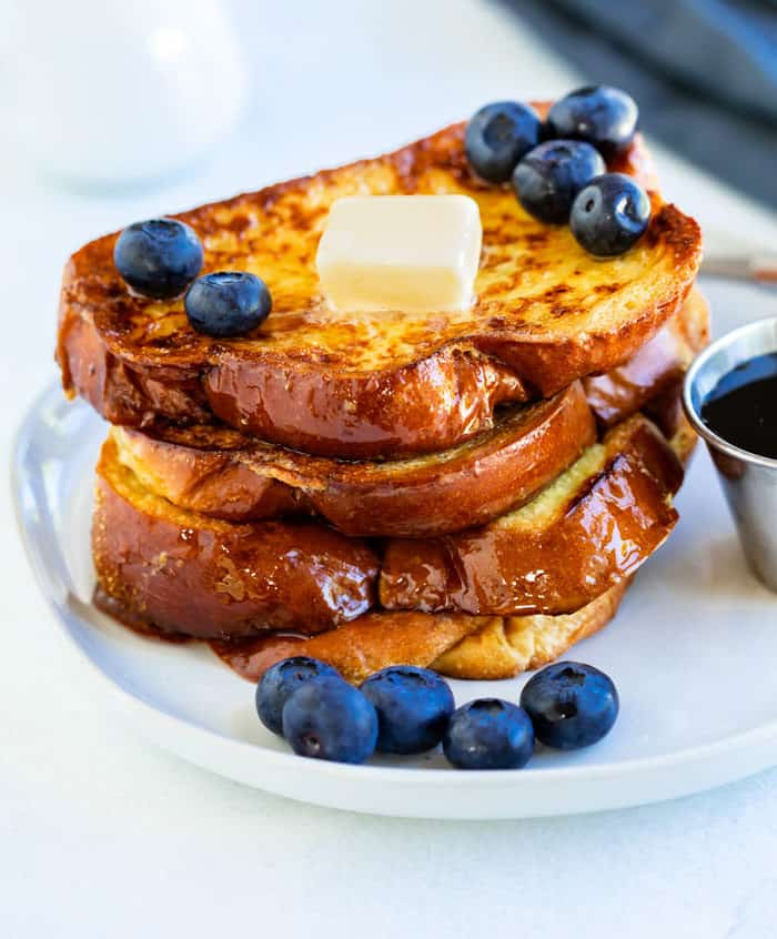 A stack of golden french toast on a white plate with blueberries and butter on top.