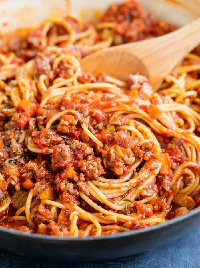 A pot with a wooden spoon stirring spaghetti bolognese.