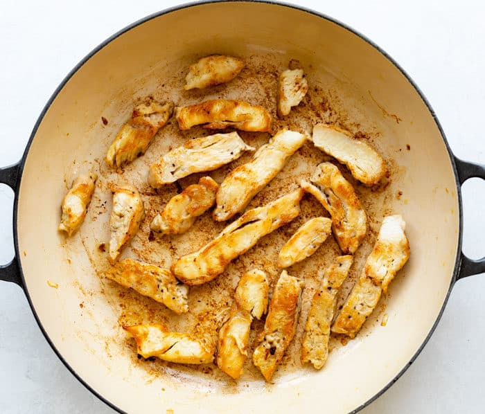 overhead view of cooked chicken strips in a pan.