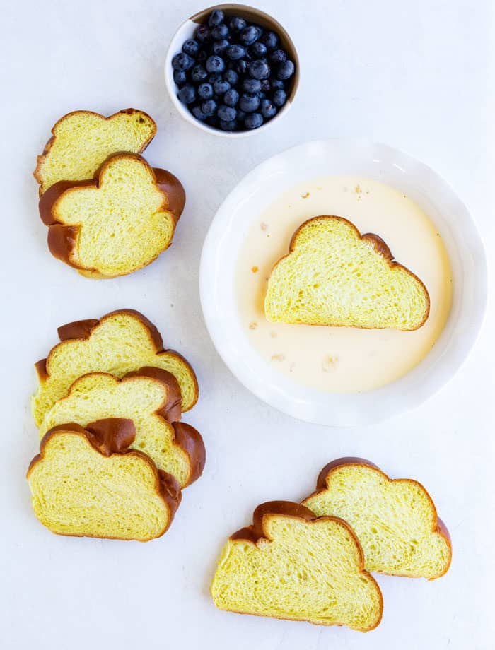 Challah bread slices being dipped into French toast custard on white table next to a bowl of blueberries.