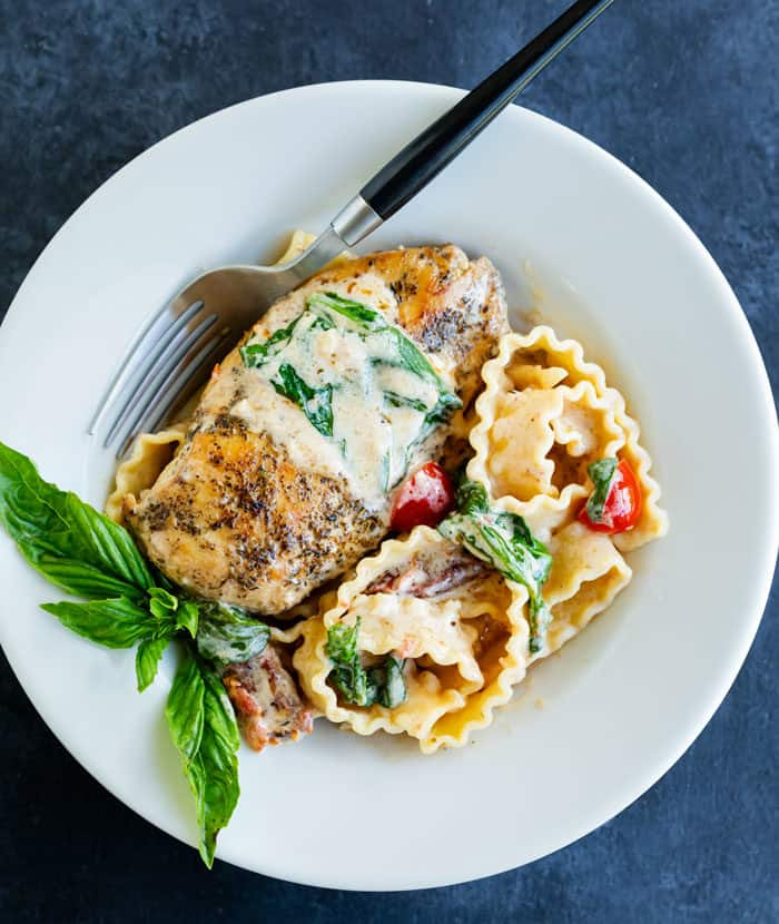 A white plate with a seasoned chicken breast and creamy pasta with a garnish of fresh basil.