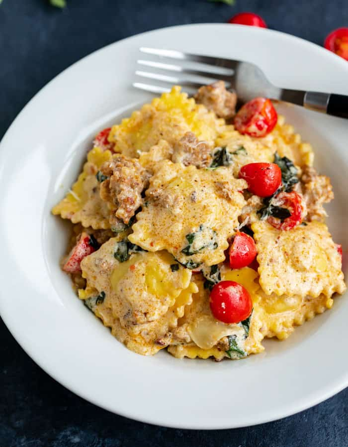 Creamy Ravioli in a white bowl with a fork in the background and cherry tomatoes on top.