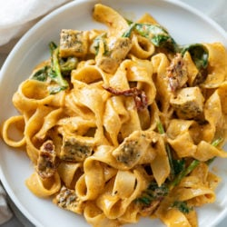 A white plate topped with creamy Tuscan Chicken Pasta with spinach and chicken.