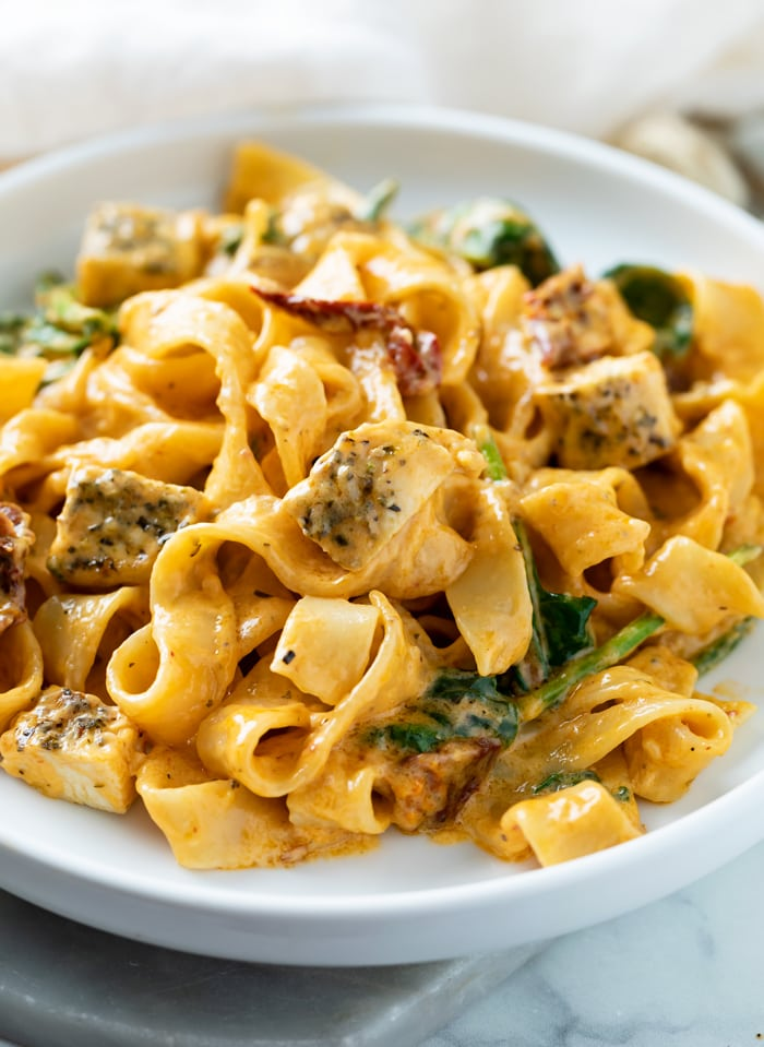 A white plate with Creamy Tuscan Chicken Pasta with noodles, chicken, sundried tomatoes, and spinach.