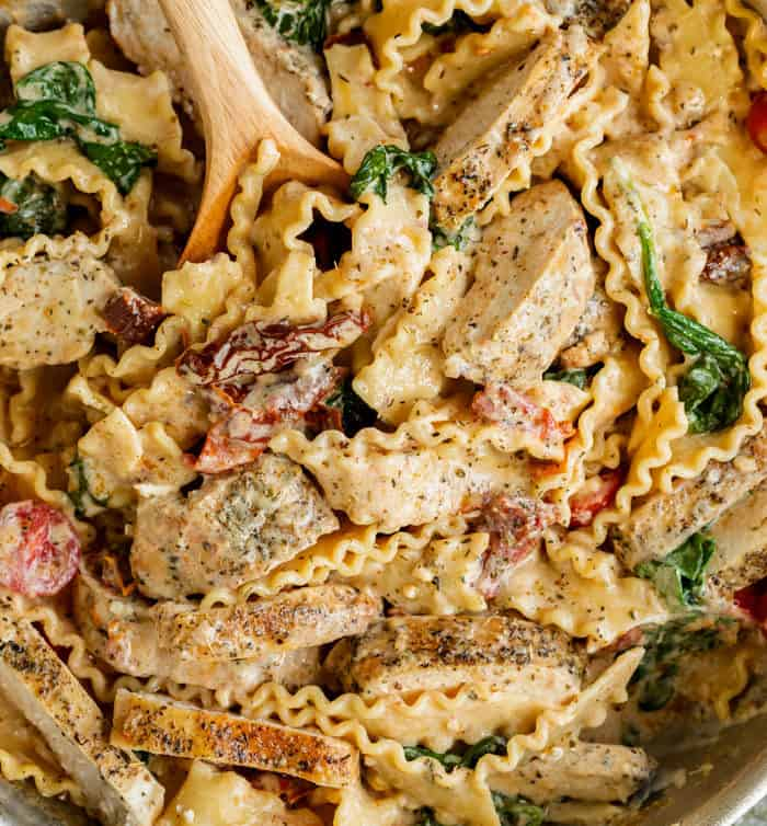Close up view of creamy noodles and chicken strips in a skillet of Tuscan chicken pasta.